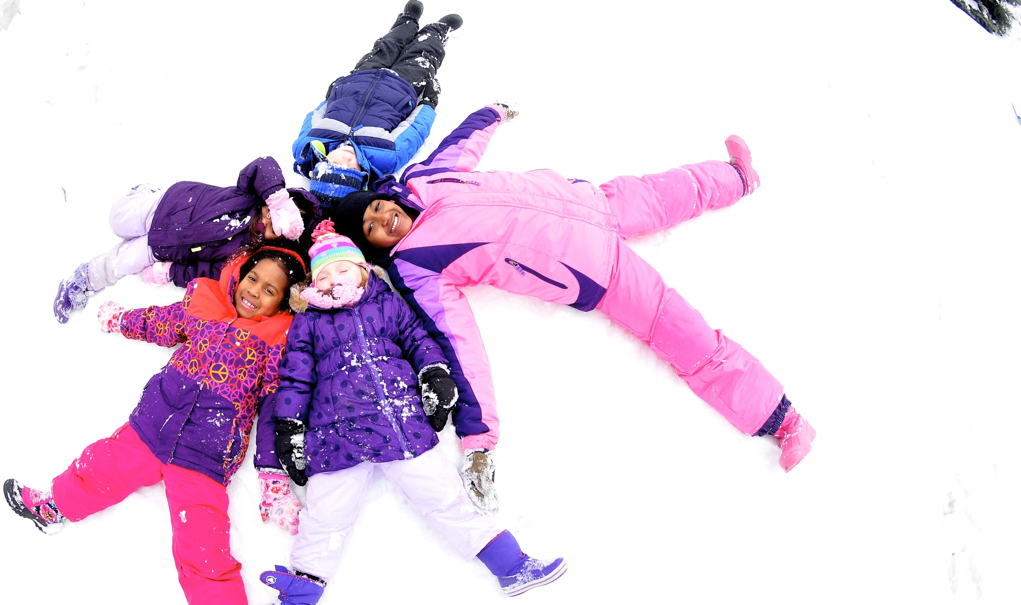 kids laying in snow in circle